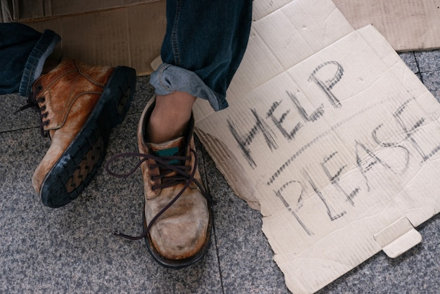 Shoes of homeless people with cardboard text