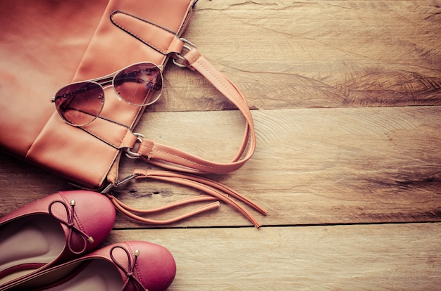 Shoes and leather bags for woman placed on a wooden floor.