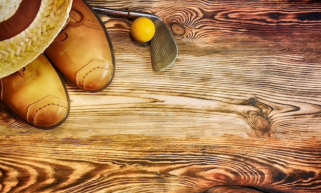 Shoes, straw hat, golf ball on the wooden background