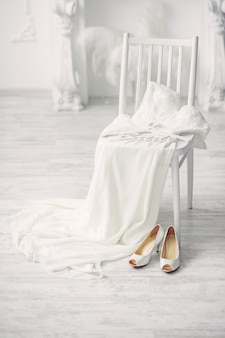 Shoes and wedding dress on chair in room