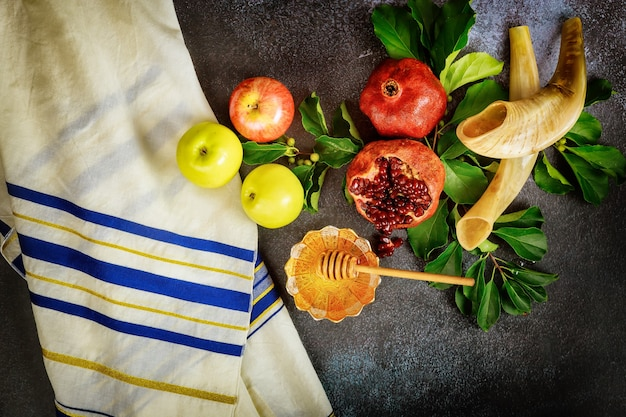 Shofar and food with talit for jewish holiday rosh hashanah. top view.