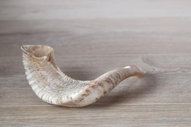 Шофар (рог) на деревянном фоне. традиционный символ праздника.