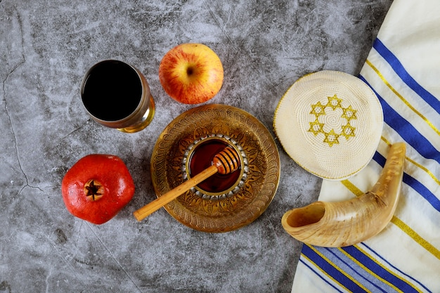 Shofar and tallit with glass honey jar and fresh ripe apples. jewish new year symbols. rosh hashanah