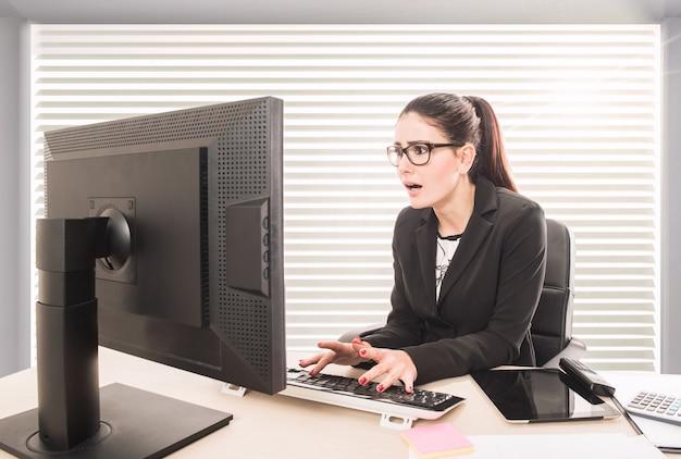 그녀의 컴퓨터에서 작업하는 충격된 비즈니스 여자