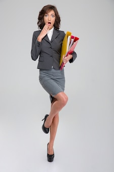 Shoked young curly pretty woman in gray costume standing on one leg in heel shoes and holding binders