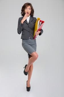 Шокированная молодая кудрявая симпатичная женщина в сером костюме стоит на одной ноге в туфлях на каблуках и держит в руках папки