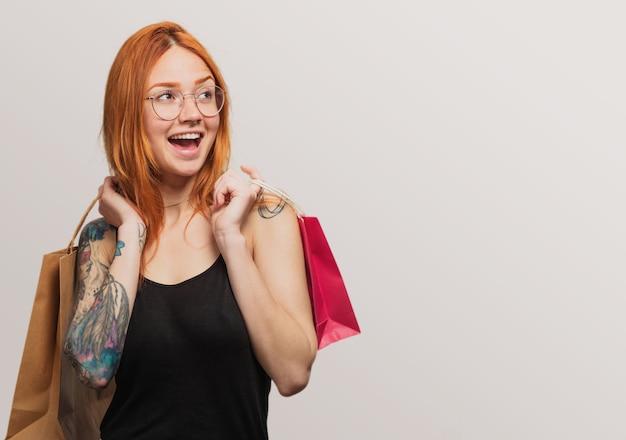 Портрет довольно рыжая девушка держит shooping сумки