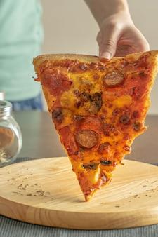 Снимайте крупным планом пиццу с начинкой пепперони, поднимаемую с круглого деревянного подноса на подставку из черной ткани и группу трав и специй в банках рядом