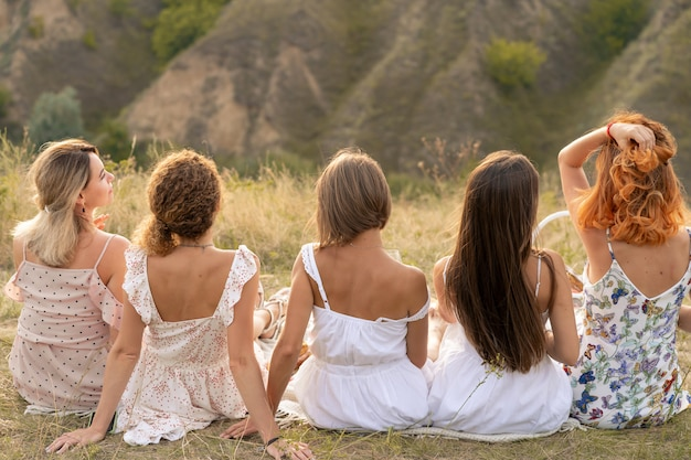 Shoot from back. the company of female friends having fun and enjoy hills landscape.