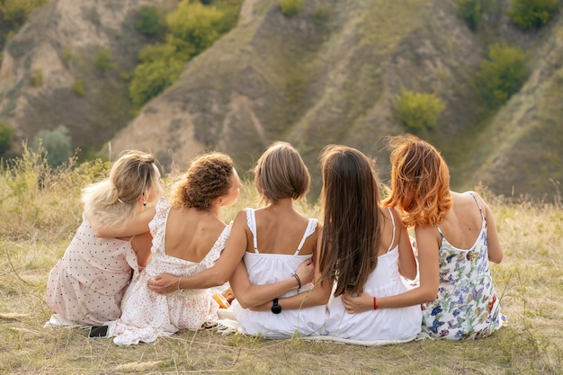 Shoot from back. the company of female friends having fun, hugs each other and enjoy hills landscape