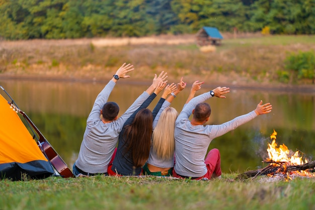 Shoot from back. a group of happy friends camping at riverside, dancing hold hands up  and enjoy view. holidays fun