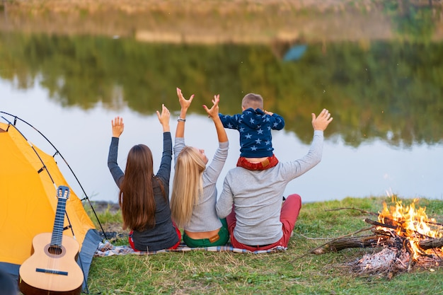 Shoot from back. a group of happy friends with child on shoulder camping at riverside, dancing hold hands up and enjoy view. family holidays fun