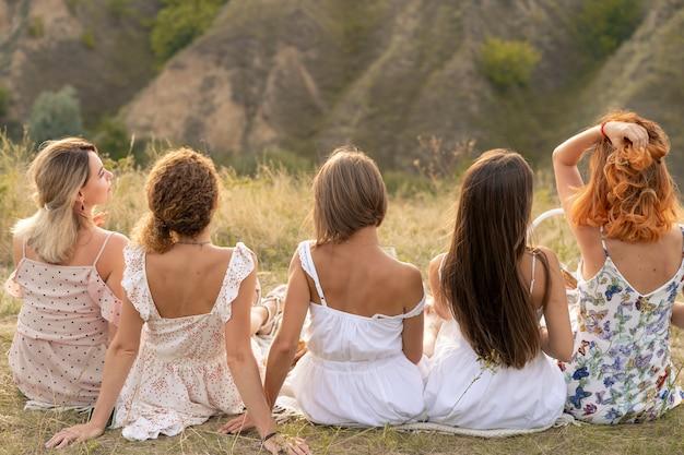 Стреляй со спины. компания подруг веселиться и наслаждаться пейзажами холмов.