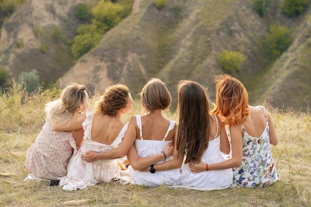 Стреляй со спины. компания подруг весело проводит время, обнимает друг друга и наслаждается пейзажами холмов