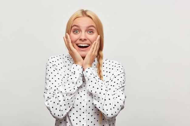 Снимок красивой блондинки с волосами, заплетенными в косу, испытывает восторг энтузиазма