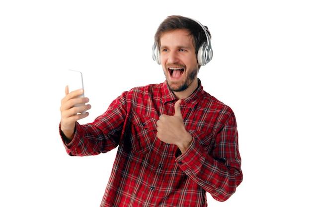 モバイル スマート フォン、白いスタジオの背景に分離されたヘッドフォンを使用して若い白人男性の撮影。現代のテクノロジー、ガジェット、テクノロジー、感情のコンセプト