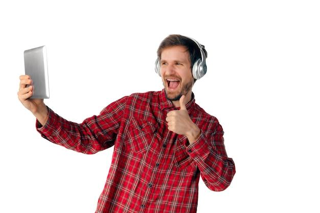 태블릿 및 흰색 스튜디오 배경에 고립 된 헤드폰을 사용 하여 젊은 백인 남자의 촬영. 현대 기술, 가제트, 기술, 감정의 개념