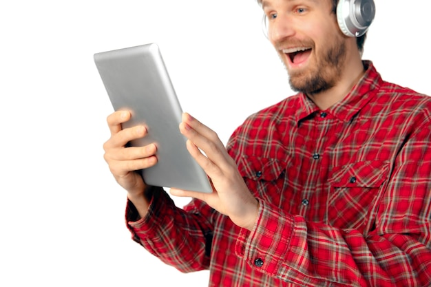 白いスタジオの壁に分離されたタブレットとヘッドフォンを使用して若い白人男性の撮影。現代のテクノロジー、ガジェット、テクノロジー、感情、広告の概念。コピースペース。クレイジーハッピー、サーフィン。