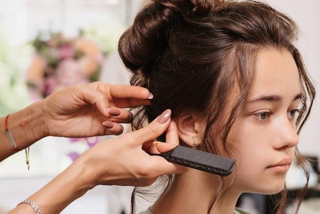 Съемка в салоне красоты. парикмахер поправляет прическу молодой темноволосой девушки с помощью гребня.