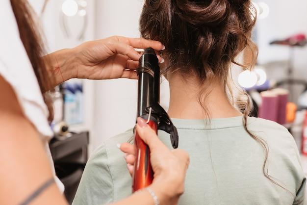 Съемка в салоне красоты. парикмахер делает прическу молодой темноволосой девушке с помощью плойки.