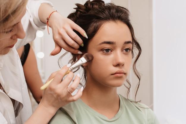 Съемка в салоне красоты. мастер-визажист наносит румяна, хайлайтер и скульптор на кожу девушки модели.