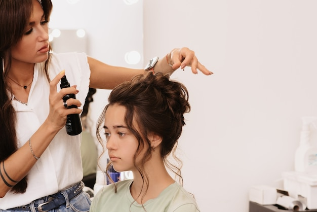 Съемка в салоне красоты. мастер-стилист делает прическу темноволосой девушке с помощью фиксации спреем-лаком для волос.