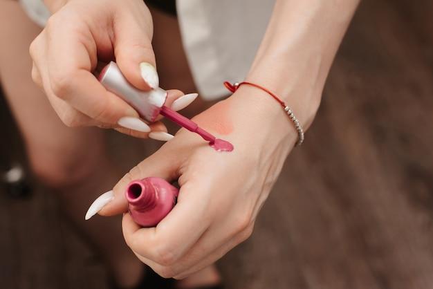 Съемка в салоне красоты. изображение рук визажиста, набирающего кистью косметический продукт.