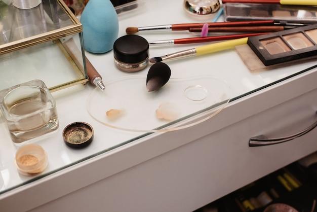 Съемка в салоне красоты. снимок рабочего места визажиста с разложенными профессиональной косметикой и кистями.