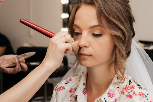 Съемка в салоне красоты. визажист наносит макияж молодой красивой девушке-невесте.