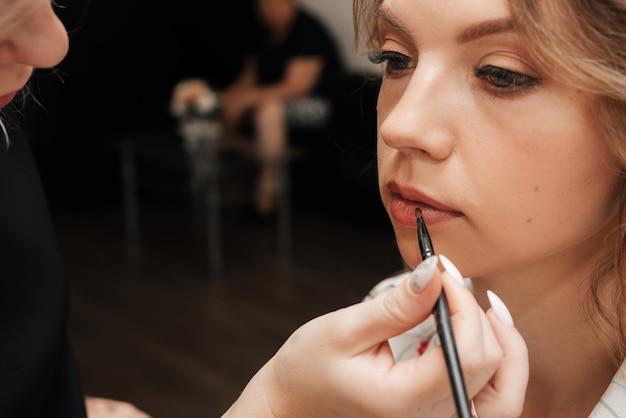 Съемка в салоне красоты. визажист наносит макияж молодой красивой девушке-модели