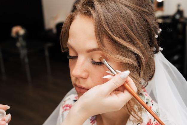 Съемка в салоне красоты. визажист наносит макияж молодой красивой девушке-модели.