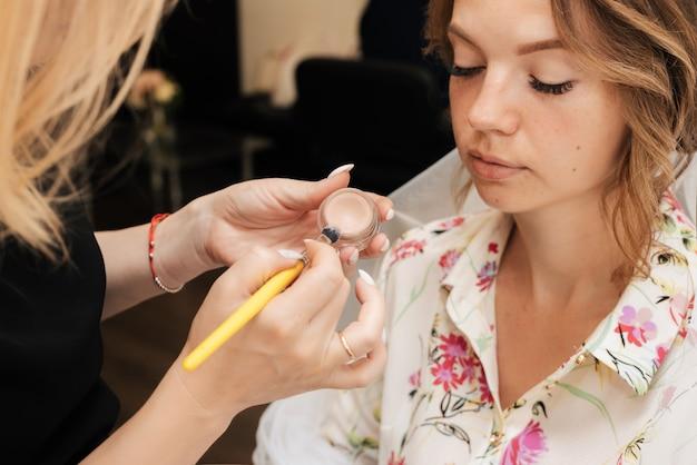 Съемка в салоне красоты. визажист делает свадебный макияж молодой красивой девушке.