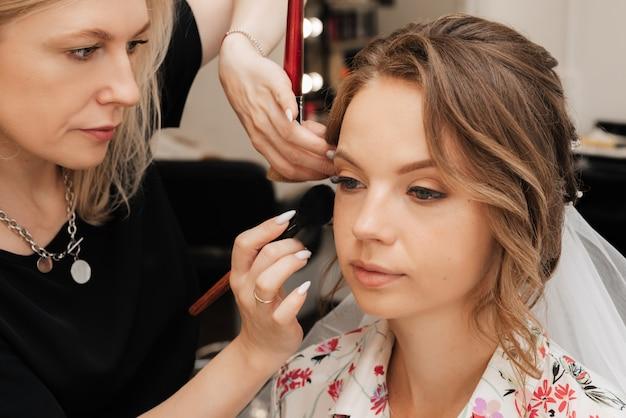 Съемка в салоне красоты. визажист делает молодой девушке свадебный макияж.
