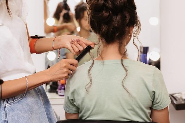 Съемка в салоне красоты. мастер-парикмахер корректирует прическу молодой темноволосой девушки с помощью расчески.