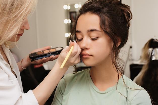 Съемка в салоне красоты. визажист наносит на глаза блестящий пигмент с помощью пушистой кисти.