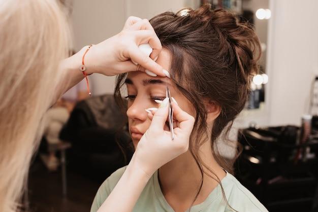 Съемка в салоне красоты. мастер-мастер выщипывает волоски, придавая бровям модели правильную форму.