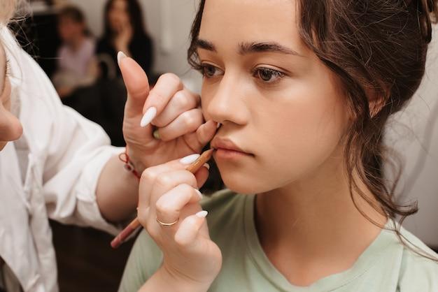 Съемка в салоне красоты. мастер-визажист закрашивает губы модели карандашом для губ.
