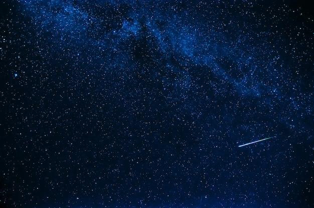 밤에 별이 빛나는 푸른 하늘 배경에서 슈팅 스타