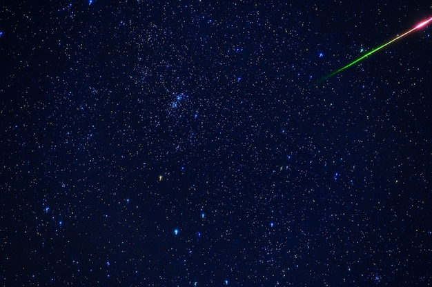 Shooting star meteorite comet on the background of a blue dark starry sky with galaxies and nebulae