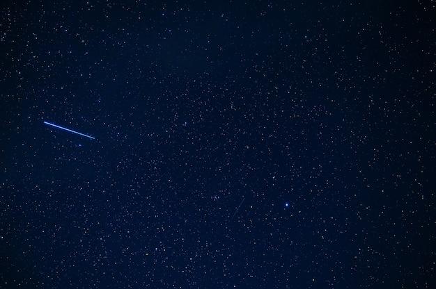 銀河と星雲のある青い暗い星空を背景にした流れ星隕石彗星