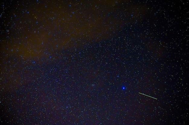 Падающая звезда метеорит-комета на фоне синего темного звездного неба с галактиками и туманностями