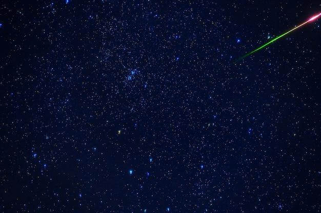 은하와 성운이 있는 푸른 어두운 별이 빛나는 하늘 배경에 유성 운석 혜성