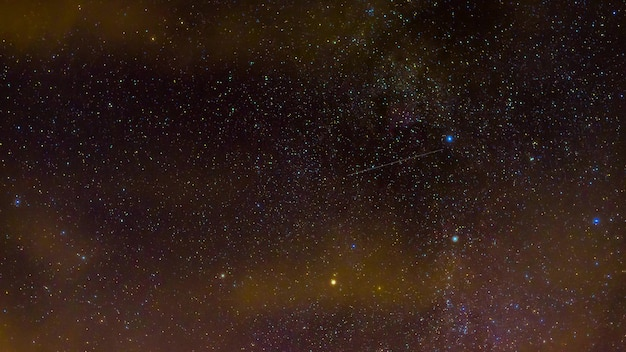 Shooting stars on the background of the milky way, galaxies and constellations at night. timelapse of the night starry sky with clouds