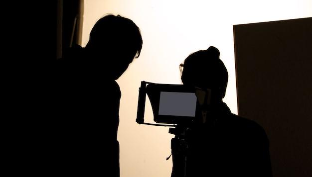 Съемочная студия за кадром в силуэтных изображениях, над которыми работает съемочная группа для съемок фильма
