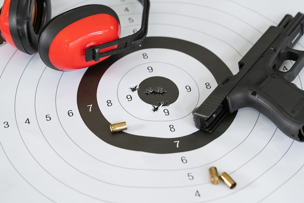 Shooting target and bullseye with bullet holes with automatic pistol gun and cartridge bullet.