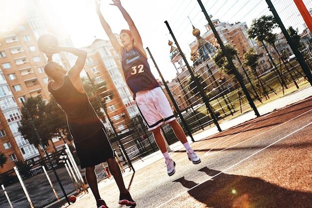 후프 촬영. 야외에서 시간을 보내는 동안 농구를하는 스포츠 의류에 두 젊은 남자