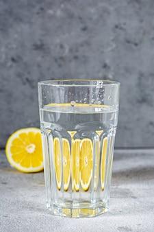 水でガラス物体を撃ちます。灰色の壁に水が入ったガラスのコップを通して反射するオレンジ(レモン)。