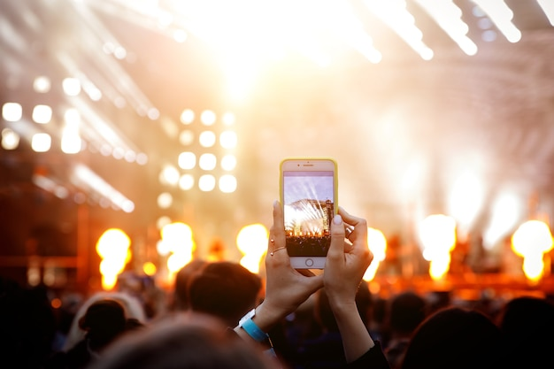 Shooting video or photo at concert. smartphone in hands.
