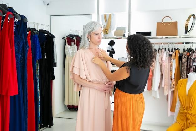 Assistente di negozio che adegua l'abito sul cliente femminile. donna che prova sui vestiti nel negozio di moda. acquisto di vestiti nel concetto di boutique