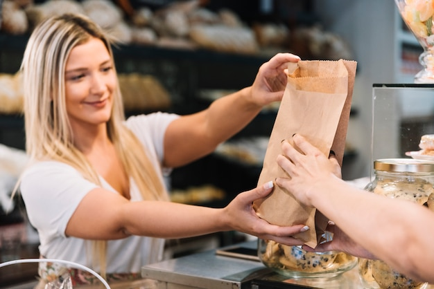 Shop assistant giving croissant bag